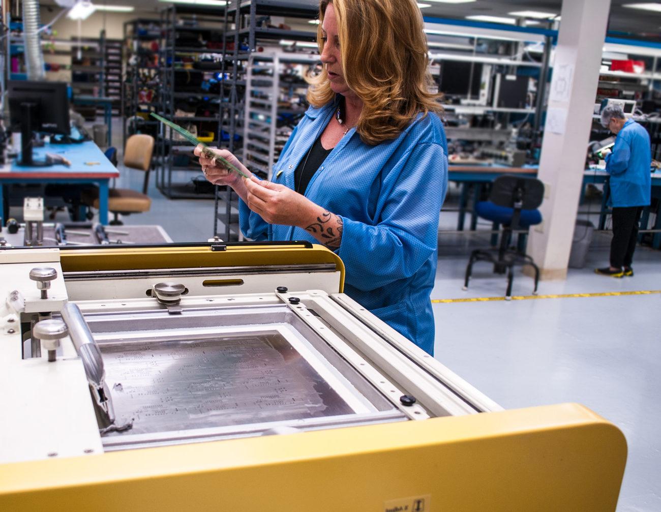 Woman examines soldering board